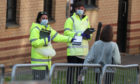 NHS staff hand out test kits to Glasgow University students as they arrive for testing at a pop up test centre at the Murano Street Student Village