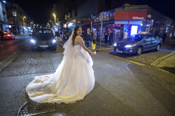 Bride Rowan races for her taxi to beat the curfew in Glasgow's West End on Friday