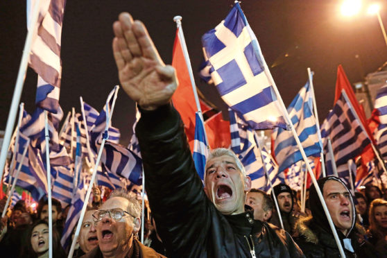 Golden Dawn supporter makes Nazi salute at a rally in Athens.