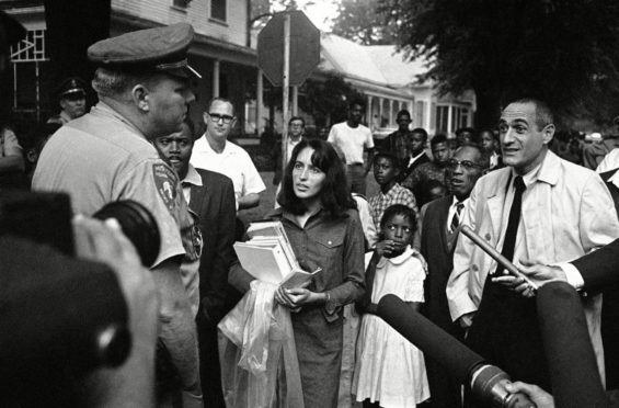 Joan Baez confronts a highway patrolman as she carries a girl's books to school in Mississippi in 1966 as she campaigns against racial segregation