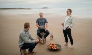 Rowers Lachlan, Jamie and Ewan MacLean enjoy a taste of their two unique whiskies on Tyninghame Beach, near North Berwick