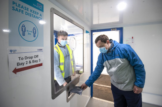 Andrew Ilesley collects a self-test kit during a  demonstration on how to use the new walk-through Covid testing centre in Dundee
