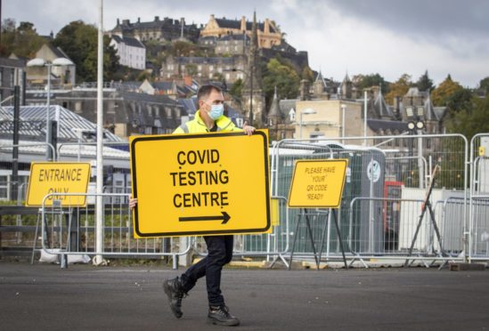 Jim Connell sets up signs at a new walk-through Covid test centre at The Engine Shed, Stirling, which opened to the public this weekend