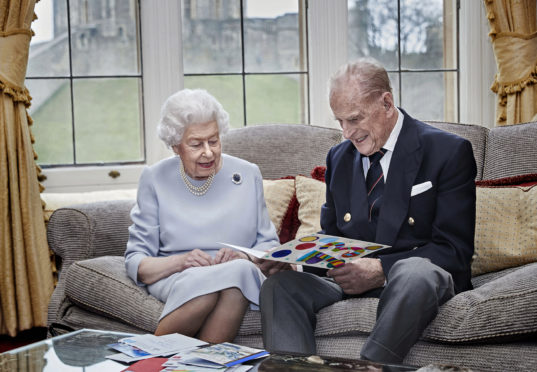 Queen Elizabeth II and the Duke of Edinburgh in the Oak Room at Windsor Castle, Berkshire, looking at their homemade wedding anniversary card, given to them by their great grandchildren Prince George, Princess Charlotte and Prince Louis, for their 73rd wedding anniversary on November 20.