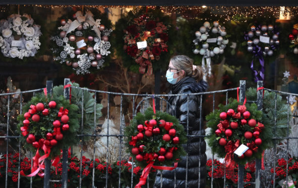 A person wearing a face covering walks passed Christmas wreaths for sale at All Occasions Designer florist in Denny