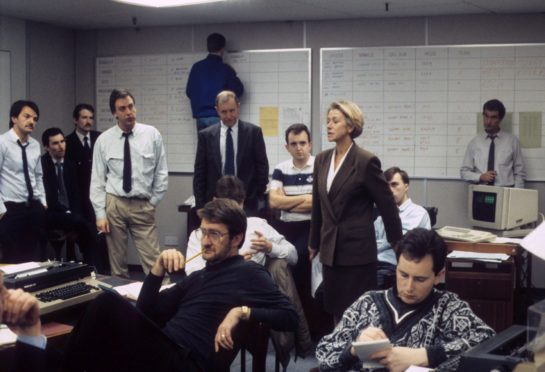 Actress Helen Mirren as Jane Tennison surrounded by men in TV's Prime Suspect