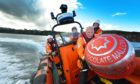 Sir Boyd Tunnock and one of his famous teacakes with crew on St Abbs lifeboat