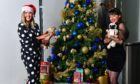 STV presenters Polly Bartlett and Laura Boyd pose next to the Christmas tree at STV studios