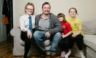 Richard Neville at home in Paisley with daughters, from left, Katie, 13, Sophie, 7, and Holly, 10