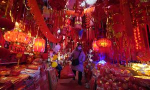 A masked vendor walks through a market decorated for Chinese New Year in Wuhan in China's Hubei province.  One year ago yesterday, a notice sent to smartphones in the city announced the world's first coronavirus lockdown. Now life has largely returned to normal for the 11 million residents of the city where Covid-19 was first detected. Wuhan accounted for the bulk of China's 4,635 deaths, but has been largely free of further outbreaks since lockdown was lifted on April 8. Questions, however, remain over the virus's origins – and the authorities' response.