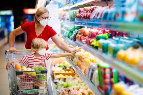 A mother and her little boy buy fresh vegetables in a supermarket. One store manager said groups of people are coming in for a chat in the aisles