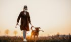A woman in protective mask walks her pet dog in the countryside