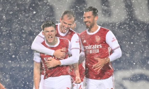 Kieran Tierney celebrates scoring against West Brom in his short-sleeves in the snow