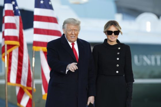 President Donald Trump gestures as first lady Melania Trump looks on before giving a speech to supporters at Andrews Air Force Base, Md., Wednesday, Jan. 20, 2021.