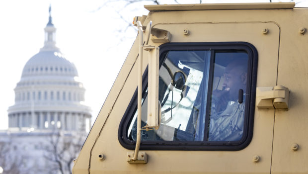 A National Guard soldier sits in a military vehicle near the US Capitol building in Washington DC as security tightens ahead of Wednesday's inauguration of Joe Biden
