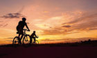 Silhouetted cyclists enjoy a peaceful run-out at sunset