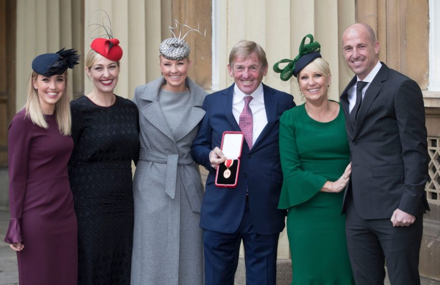 His family join Kenny at the palace when he was knighted in 2018