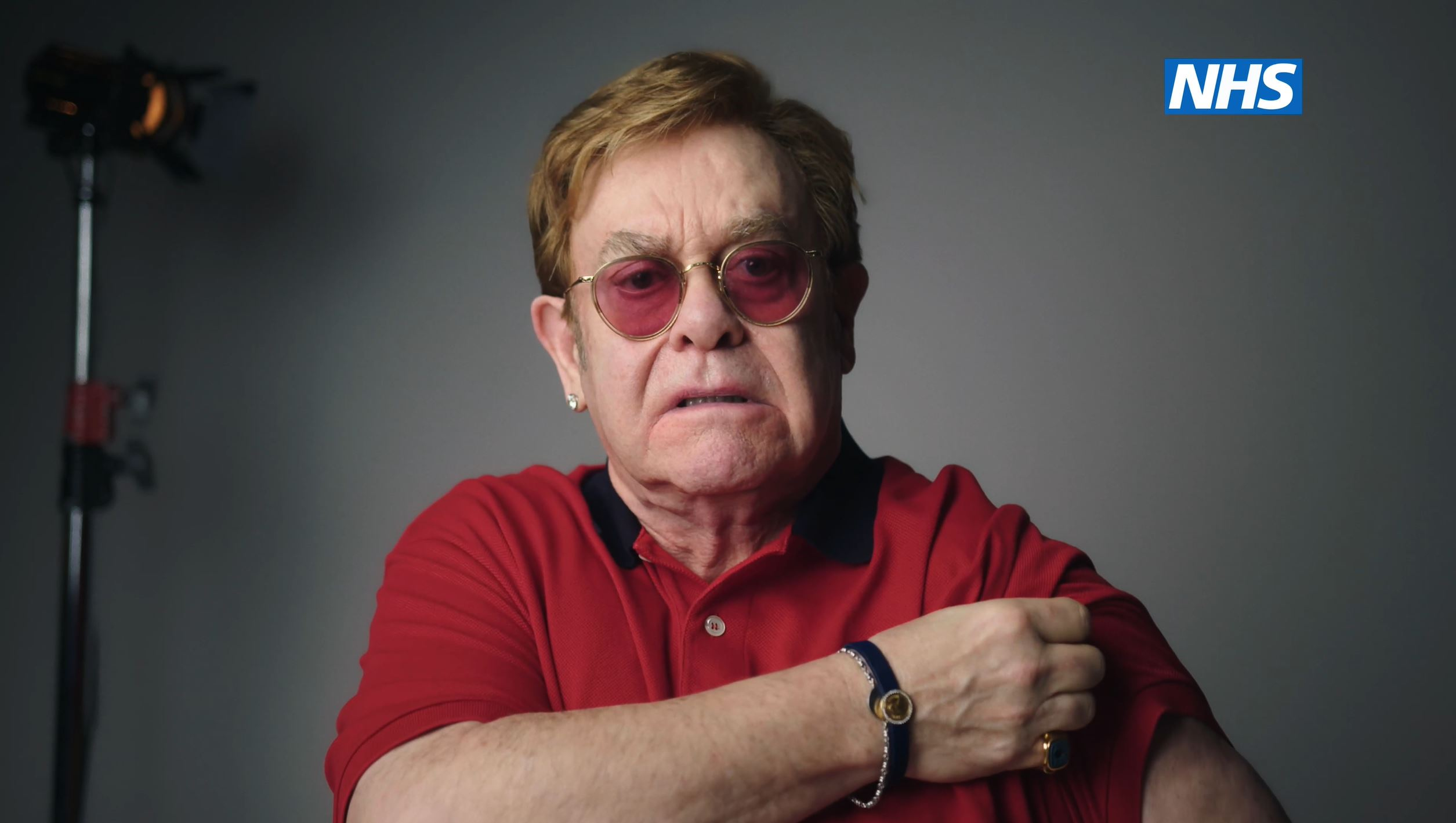 Sir Elton John rolls his sleeve up for the vaccine ad