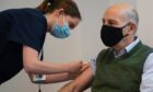Broadcaster and author Loyd Grossman, 70, receives an injection of the Oxford AstraZeneca Covid-19 vaccine.