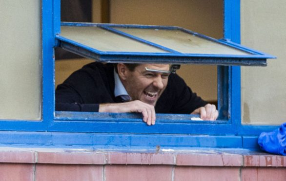 Rangers manager Steven Gerrard looks out of the dressing room window to fans gathered outside Ibrox