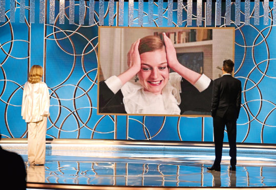 Emma Corrin (c) accepts the Best Television Actress - Drama Series award for 'The Crown' via video from Kyra Sedgwick (l) and Kevin Bacon at the 78th Annual Golden Globe Awards held at the Beverly Hilton Hotel.
