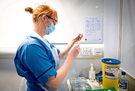 Nurse Eleanor Pinkerton prepares a coronavirus vaccine to be given to a health and care staff member at the NHS Louisa Jordan Hospital in Glasgow, as part of a mass vaccination drive by NHS Greater Glasgow and Clyde.