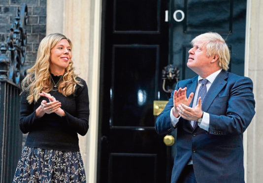 Boris Johnson taking part in the Clap for our Carers with his partner Carrie Symonds.