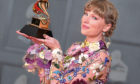 Taylor Swift poses with the award for album of the year for Folklore at the 63rd annual Grammy Awards