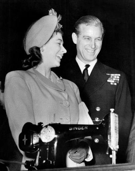 Duke of Edinburgh and Queen Elizabeth II receiving a wedding present of an electric sewing machine at Clydebank Town Hall where they were launching the liner Caronia.