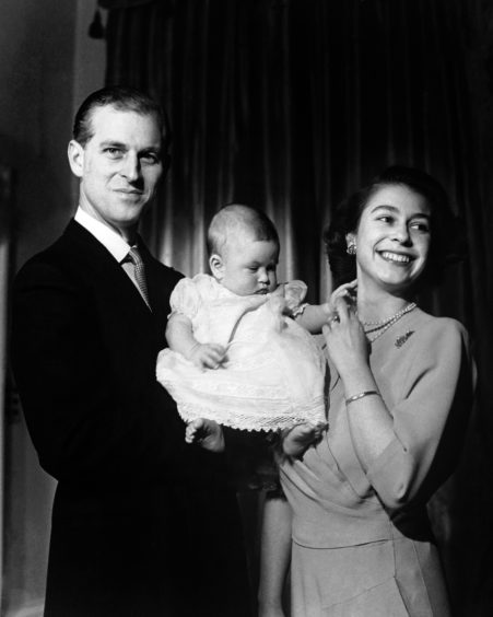 Queen Elizabeth II and the Duke of Edinburgh holding their first child Prince Charles, aged six months in Buckingham Palace.