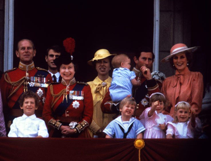 (left to right) the Duke of Edinburgh, Prince Edward, Queen Elizabeth II, Princess Anne, the Prince of Wales holding Prince Harry, the Princess of Wales, and Prince William on the balcony of Buckingham Palace, London.