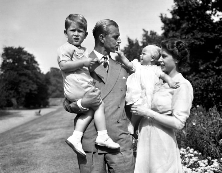 The Princess Royal in the arms of Queen Elizabeth II, with The Duke of Edinburgh, holding The Prince of Wales, in the grounds of Clarence House.