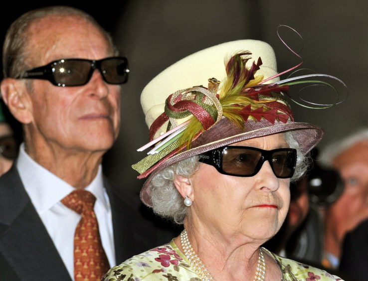 Queen Elizabeth II and the Duke of Edinburgh wearing 3D glasses to watch a 3D film, at the Pinewood Studios in Toronto, Canada.