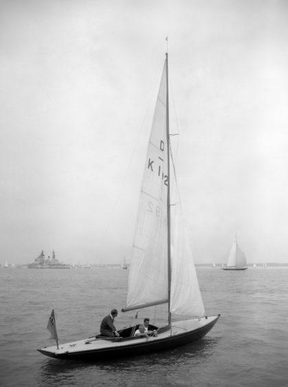 """The Duke of Edinburgh (left) leaning forward to grasp the tiller of the 'Dragon' yacht """"Bluebottle"""", which he owned jointly with the Queen, on the fourth day of the Cowes Regatta Week."""