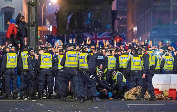 Police detain a man as Rangers fans gather at George Square in Glasgow on March 7.