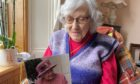 Annie Whyte reads the 100th birthday card sent to her by the Queen