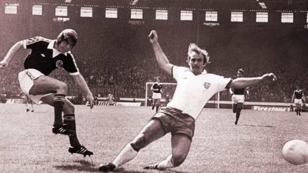 Kenny Dalgish scoring against England in 1976. The ball bobbles along the turf and then goes through Clemence's hands and then his legs.