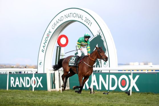Rachael Blackmore, the first woman jockey to win the Grand National, roars with delight as she clears the finishing line on Minella Times