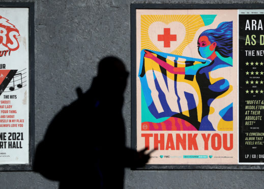 A person walks passed an advertising board in Glasgow showing a Thank You NHS poster