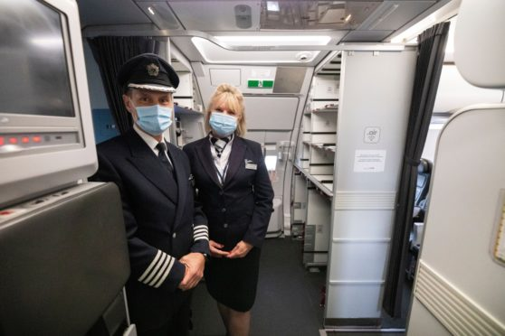Aircrew wear masks to welcome passengers back on board as Which? warns travellers to check their travel insurance cover