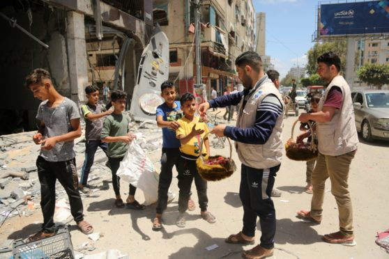 Aid workers hand out fruit and sweets to Palestinian children amid the rubble of Gaza City following days of Israeli air strikes