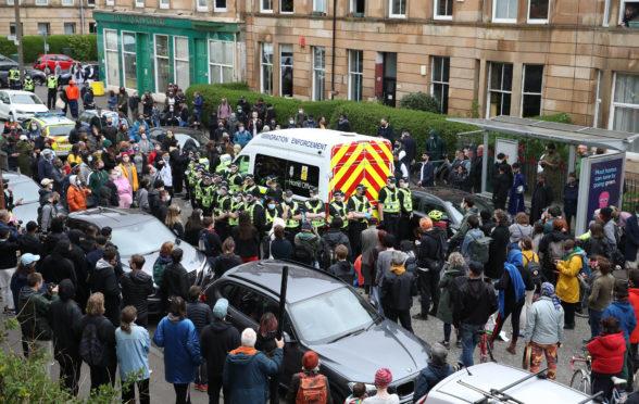 Protesters block an immigration van in Glasgow following a dawn raid in Pollokshields.