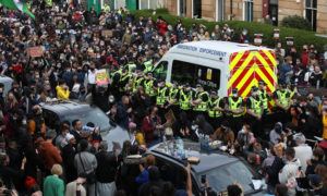 Lawyer Aamer Anwar speaks to protesters blocking the road as police surround an immigration van in Kenmure Street, Glasgow