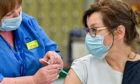 Natalyia Dasiukevich receives her Covid-19 vaccination from nurse Carol McGlion at Allander Sports Centre in Glasgow