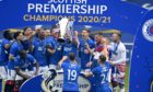 Two-goal Kemar Roofe gets his hands on the Premiership trophy with his team-mates at time up.
