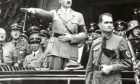 Then German Chancellor Adolf Hitler and his personal representative Rudolf Hess, right, during a parade in Berlin, Germany.