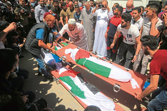 Mourners react next to bodies of Palestinians who were killed amid a flare-up of Israeli-Palestinian violence, during their funeral at the Beach refugee camp, in Gaza City.