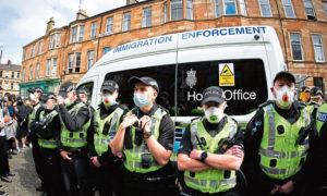 Protestors block an UK home office immigration enforcement van after an attempted raid was carried out in the morning in Kenmure Street in Pollokshields on May 13, 2021 in Glasgow, Scotland.