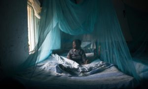 A child underneath a mosquito net, Kenya