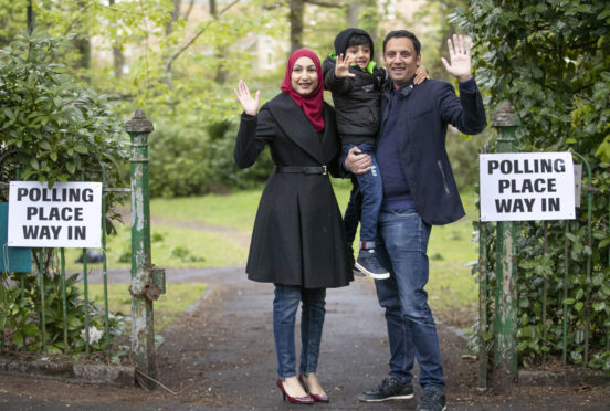 Scottish Labour party leader Anas Sarwar, with wife Furheen and son Ailyan, arrives to deliver his postal vote at Pollokshields Burgh Hall in Glasgow